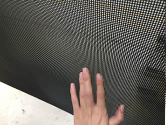 A hand beside a section of crime safe mesh.
