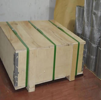 A wooden box on the floor and several rolls of unpacked wire mesh beside the box.