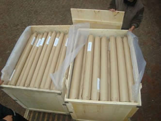 Two wooden boxes are filled with monel woven wire mesh rolls.