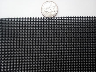 A piece of black crime safe mesh is beside a metal coin.